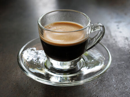 Small glass of espresso coffee on table photo