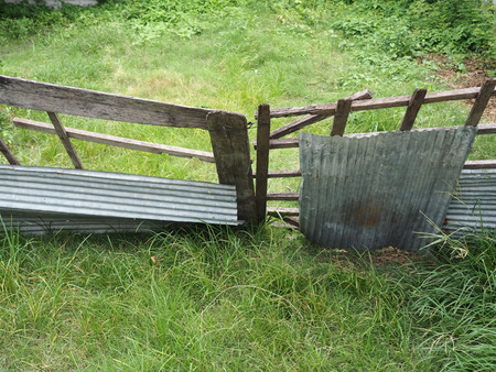 Fail and collapse wood fence on empty land Stock Photo