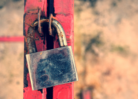 old and corroded padlock on steel, vintage color background photo