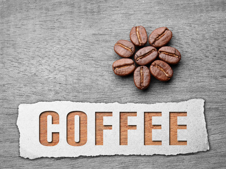 Coffee crop beans with paper and text on wood texture background photo