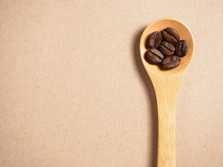 Coffee crop beans on  bamboo spoon and paper texture background photo