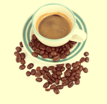 Espresso cup and coffee beans, vintage color background photo
