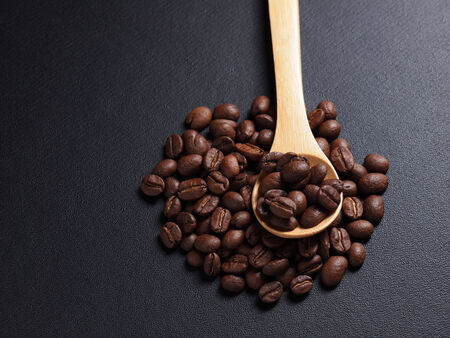 Coffee crop beans on bamboo spoon and leather texture background photo