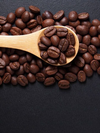 Coffee crop beans on bamboo spoon and leather texture background Stock Photo