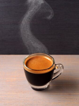 Cup of hot espresso coffee on wood board photo