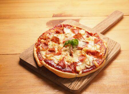 Hawaiian pizza on wood plate