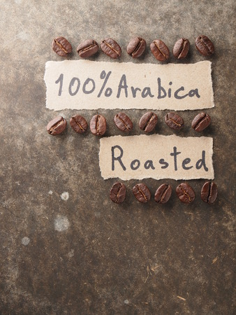 Coffee crop beans with 100 percent arabica  paper on wood texture background Stock Photo