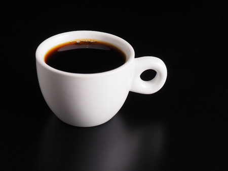White Cup of hot black coffee on table with black background