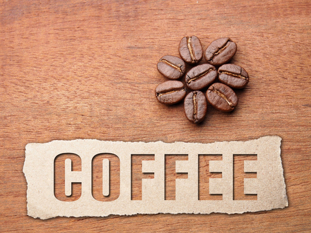 Coffee crop beans with paper and text on wood texture background Stock Photo