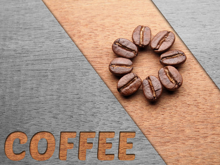 Coffee crop beans on wood texture with coffee text , background