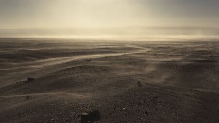 Wind and sand storm in Atacama desert. Golden dunes in the sunset light.