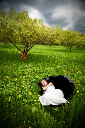Beautiful girl sleeping in the cello case in the apple garden with cello at the background photo