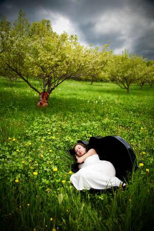cello:  Bella ragazza dormire nel caso di violoncello in giardino mela con violoncello a sfondo