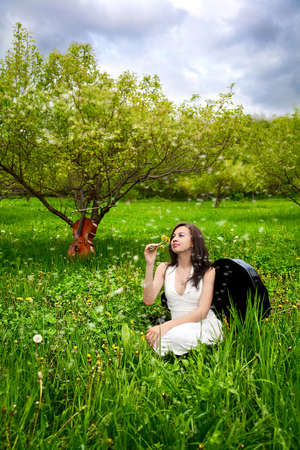snuff: Beautiful girl sitting in the cello case in the apple garden with cello at the background Stock Photo