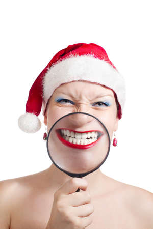 Girl smiling through magnifier in Christmas hat isolated on white background photo