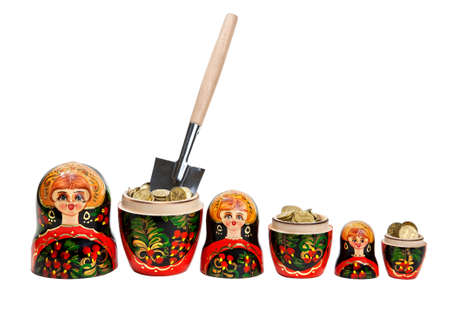 Three Matryoshkas full of coins with shovel in one of them at white background photo