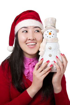 Beautiful Asian girl smiling in Christmas hat with snowman isolated on white background photo