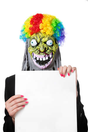 Funny monster in clown's wig with white blank banner isolated on white background photo