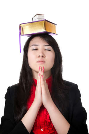 Asian girl with books on her head and prayer gesture isolated on white background photo