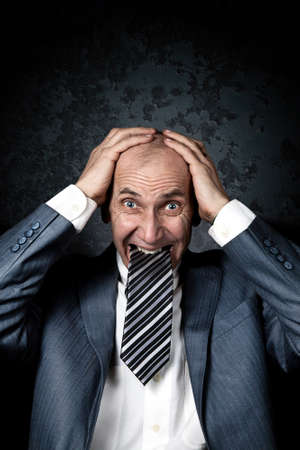 Businessman with Necktie in his mouth holding his head with hands on grunge background photo
