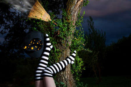 Witch in striped long socks has fallen from her broomstick at night Stock Photo - 8681192