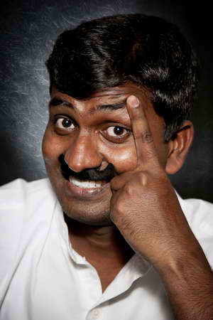 white moustache: Handsome Indian man with moustache and raise eyebrow smiling and looking at camera close-up Stock Photo