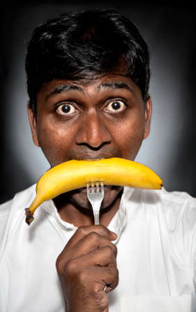 Indian hungry man eating banana in skin with fork Stock Photo - 9265243