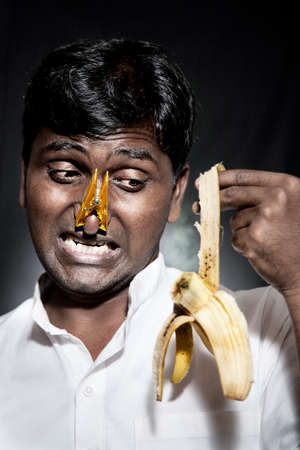 frowy: Disappointed Indian man holding rotten banana with pin on his nose at black background Stock Photo