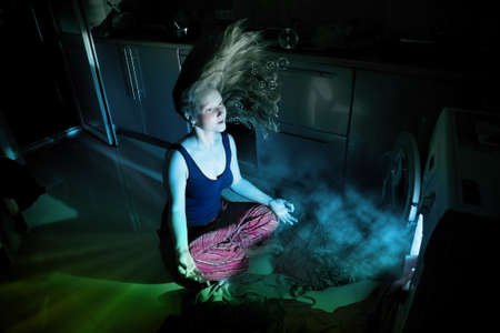 hypnosis: Frustrated woman in meditation pose near by washing machine glowing inside underwater Stock Photo