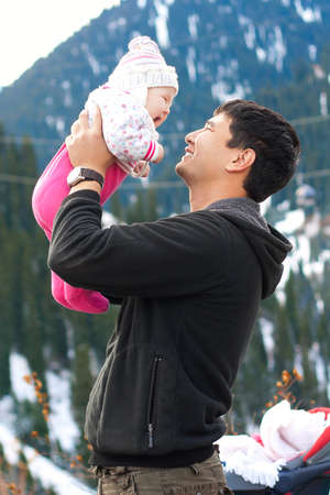 Asian father holding his baby in mountains in winter time photo