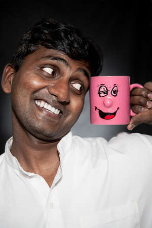 funny hair: Handsome Indian man with funny mug smiling and looking at it close-up