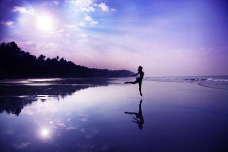 levitacion: Silueta de una hermosa joven bailando en la playa en la salida del sol en colores p�rpuras