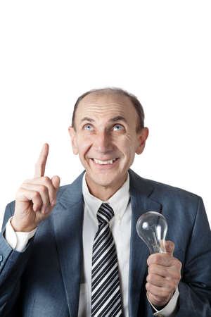 Positive mature businessman with bulb pointing up isolated on white background with free space for text photo