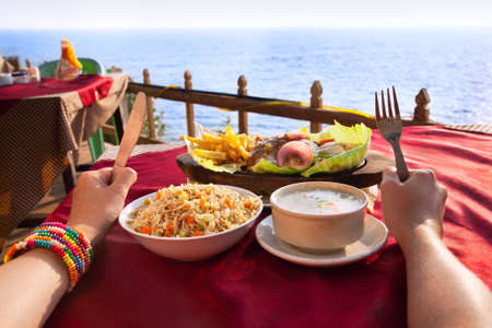 foretaste: Indian vegetarian sizzler, corn soup and fried rice on the table with ocean at the background. Hands with fork and knife on the table.