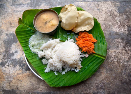 indian meal: Homemade Indian vegetarian rice, sambar, grated carrot and poppadoms on the banana leaf at grunge background