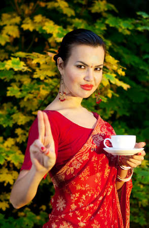 Beautiful woman in Indian red sari with cup of tea gesturing mudra outdoors  photo