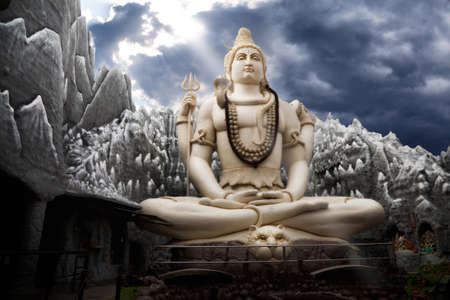 hindu god: Big Lord Shiva statue sitting in lotus with trident in his hand and cobra near by. Dramatic sky at background with ray on Shiva. Bangalore, India