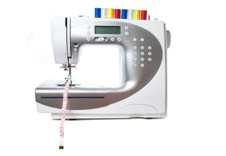 cinta de medir: M�quina de coser blanco moderna con stitchings rojo, amarillo, azul y blanco en la parte superior. Cinta m�trica en pie. Aislado en fondo blanco