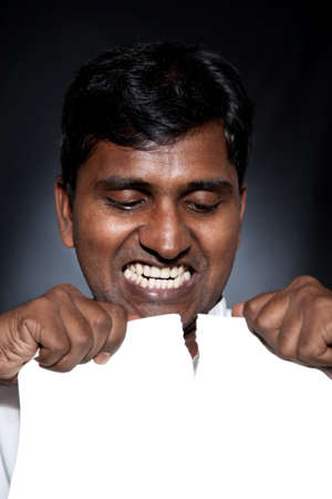 Angry Indian man tearing white blank paper sheet with free space for text photo