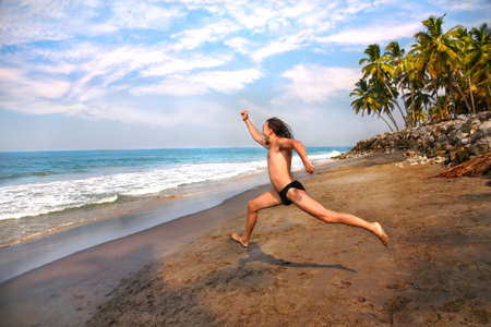Happy screaming man with long hair running on the beach to the ocean at palms background Stock Photo - 9257306