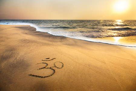 om symbol: Om symbol on the sand at the beach near the ocean Stock Photo