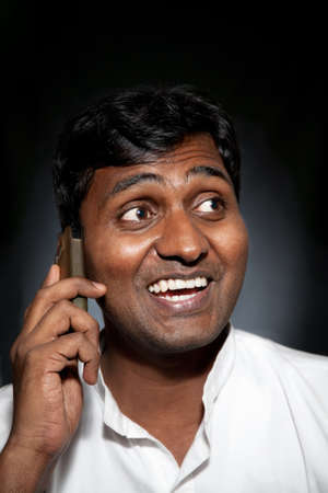 persona llamando: Hombre indio feliz hablando por tel�fono celular en fondo negro