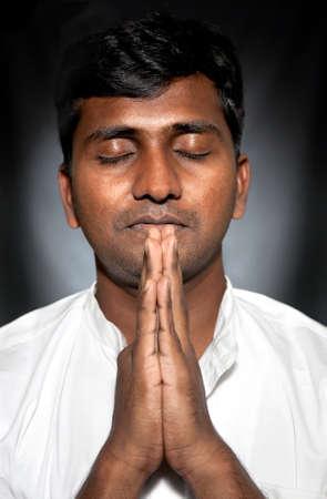 namaste: India hombre con los ojos cerrados orando y gesticular Namaste en fondo negro