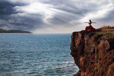 Beautiful woman doing virabhadrasana warrior yoga pose on the cliff near the ocean with dramatic sky at background in India Stock Photo