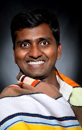 upper half: Handsome Indian man in poncho smiling and looking at camera at black background