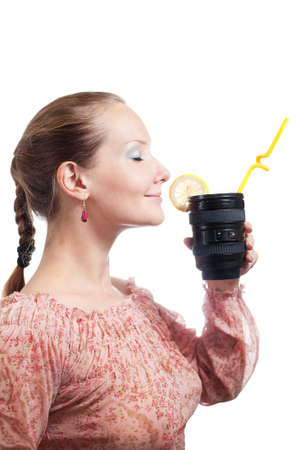 telephoto: Beautiful young woman smelling lemon on telephoto lens cup with yellow stick in it at white background.