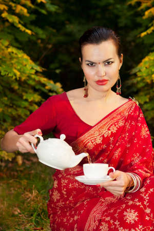 Beautiful woman in Indian red sari with teapot pouring tea into the cup outdoors in autumn time  photo