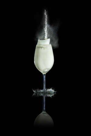 Glass of milk with splashes at black background  photo