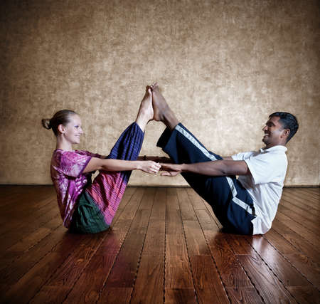 instructor: Two persons: Indian man and Caucasian woman in bright purple Indian cloth doing couple yoga nauka asana boat pose at the grunge background with wooden floor