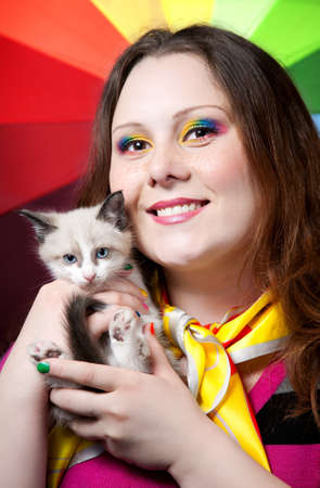 Beautiful woman with creative rainbow make-up and nails smiling and holding little kitten in her arms at rainbow background photo